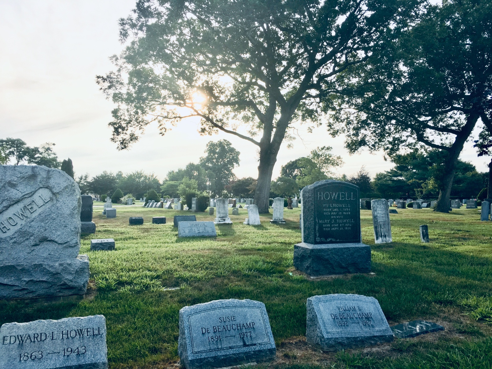 "A photo of a cemetery. In the foreground are three headstones reading ""Howell"" and two reading ""De Beauchamp."" Two tall trees stand in the background, blocking the light of a setting sun."